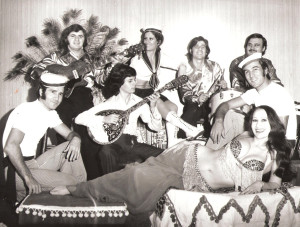 In Houston, Texas, at the Bacchanal Greek restaurant with musicians and Greek folk dancers. From left top row: Gregory Vasiliou on guitar, Katia Gicoudis, folk dancer, Takis on drums, Panagiotis on synthesizer. From left bottom row: George Gicoudis folk dancer married to Katia, Panagiotakis Kogas on bouzouki, Kostas folk dancer and Helena, around 1971 or 1972; belly dance